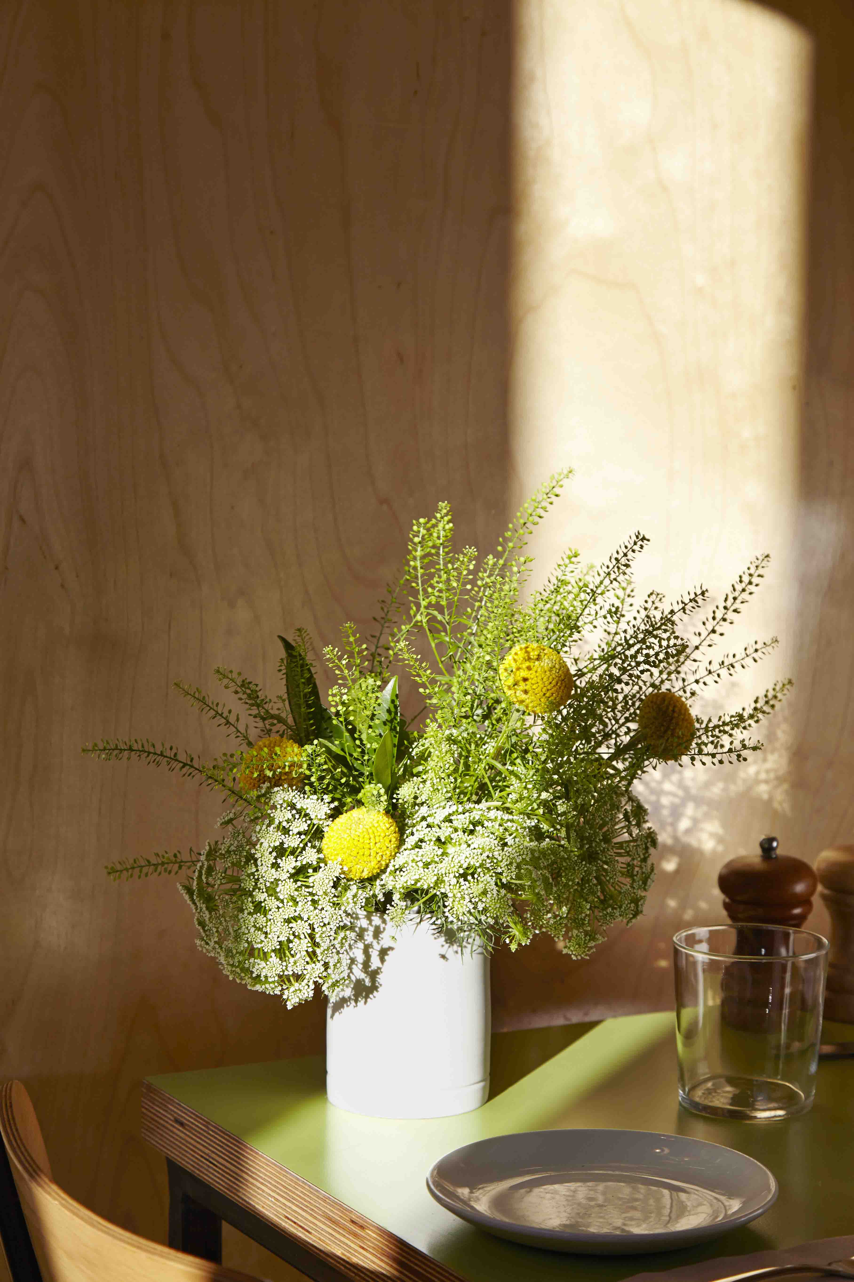 Wooden shelf with flowers in white vase on green table.