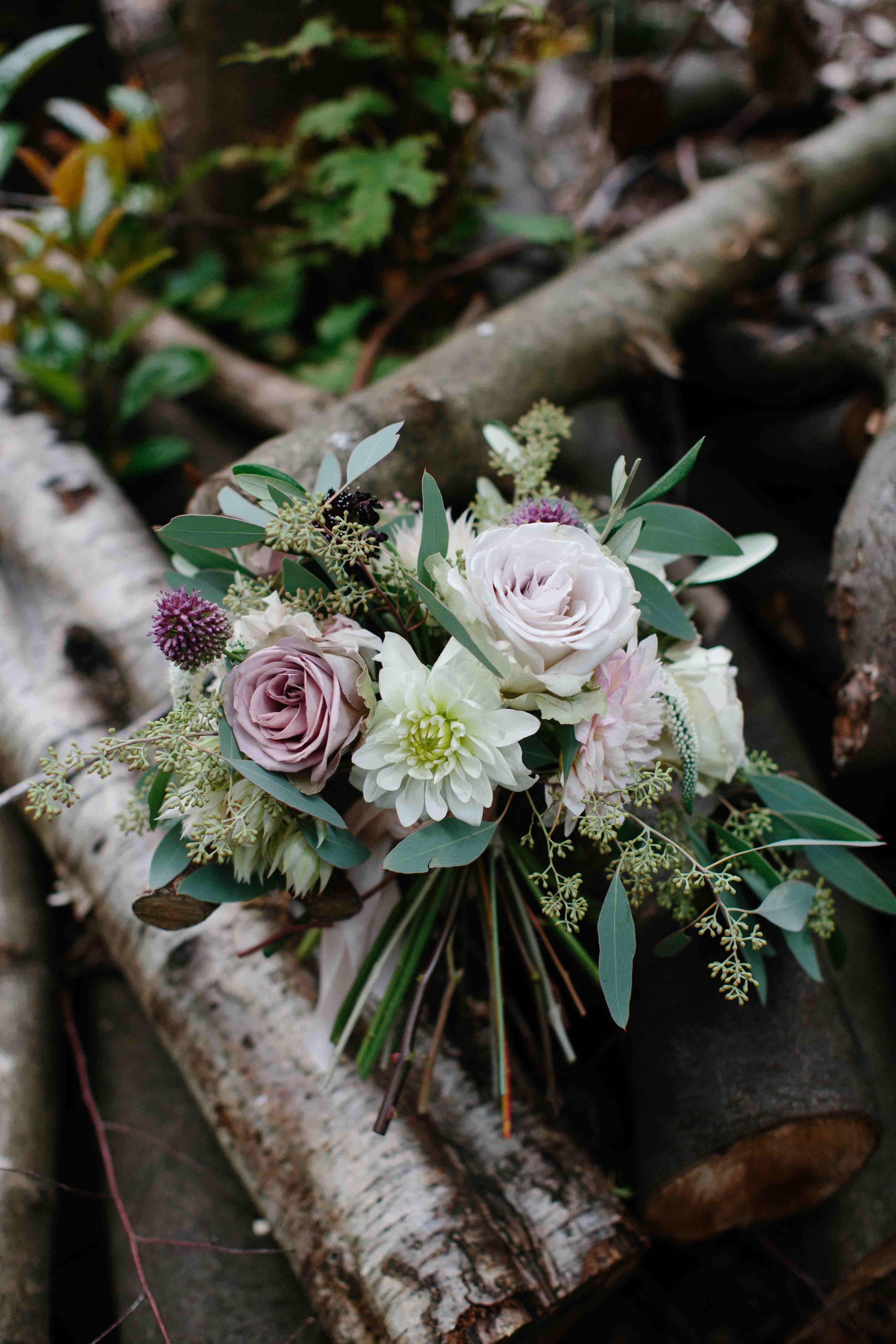 Bouquet on a pile of logs.