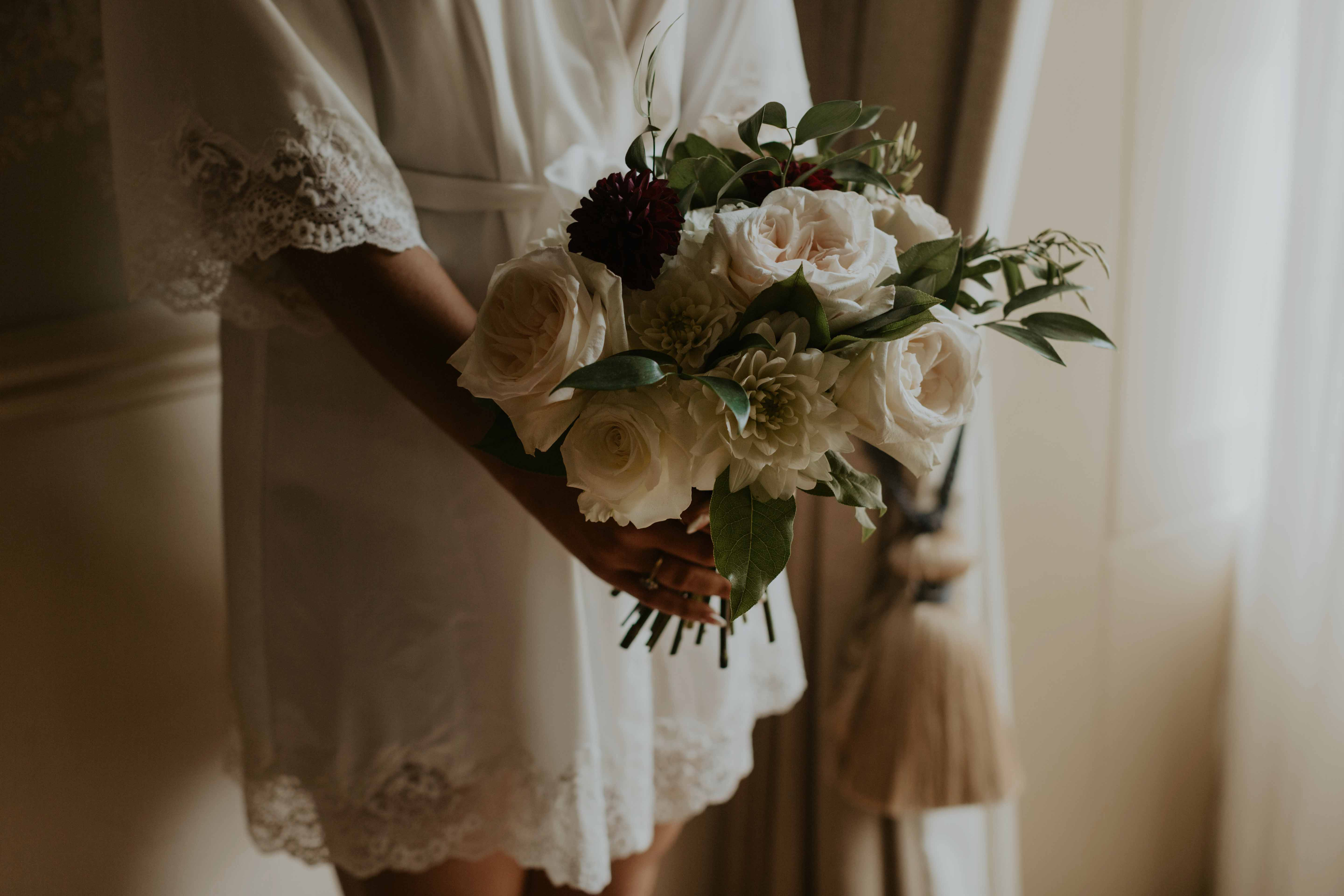Bride holding bouquet robe.