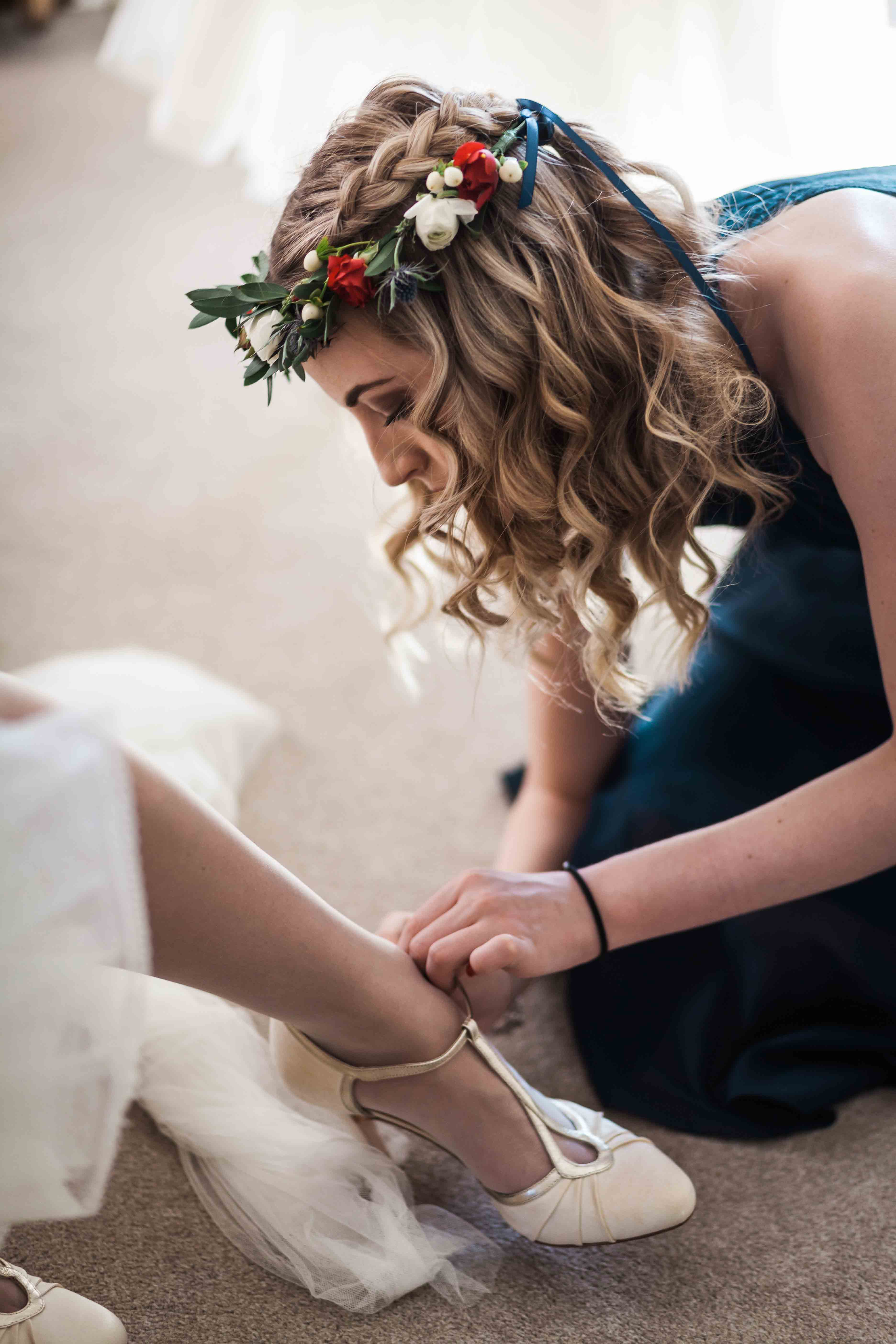 Bridesmaid with flower crown fixing brides shoe.