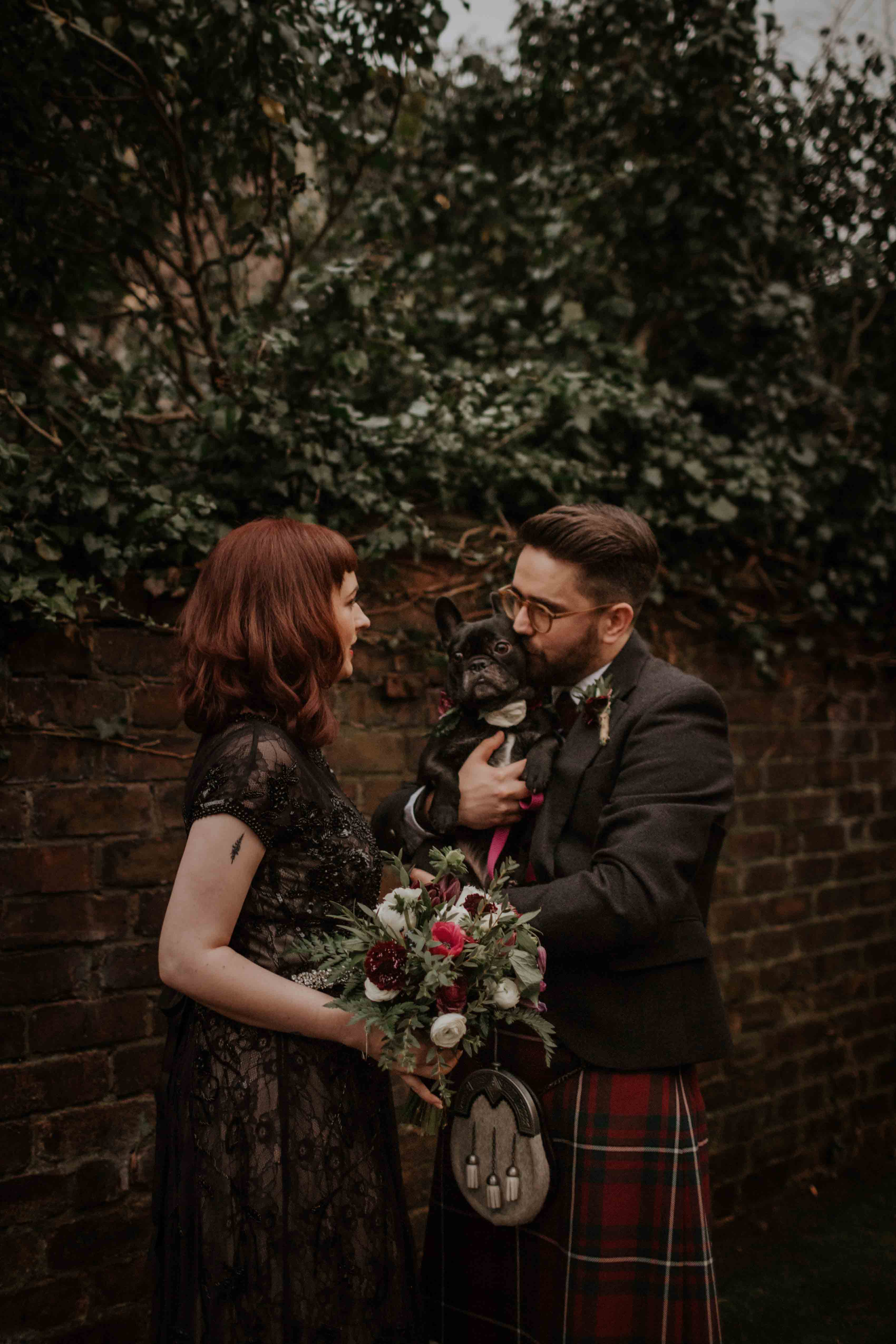 Bride with bouquet. bearded groom wearing glasses and kilt with french bulldog.